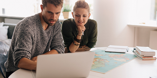 Young couple exploring courses on laptop